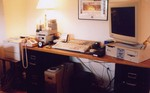 snorwood's crowded desk; dragon (main server) is Ultra 2 with monitor; DLT and 4mm tape drives are on the left and HP printer is at far left.  The keyboards are for dragon and anteater (SGI under desk).